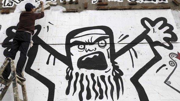 Joven Egipcio trabajando en un mural en el 2012 cuando el sentimiento en contra del Islam político alcanzó su máximo punto.